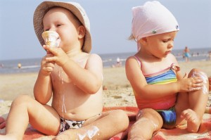 Toddlers having ice cream on the beach --- Image by © Royalty-Free/Corbis